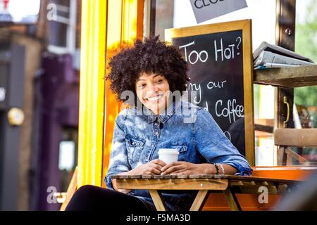 Happy mature woman drinking takeaway coffee and sidewalk cafe - Stock Photo