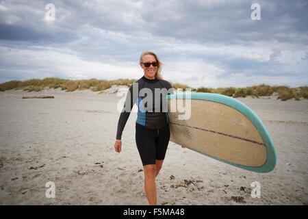 Senior woman walking on beach, carrying surfboard - Stock Photo