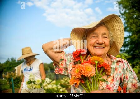 Senior woman holding onto straw hat and flowers on farm - Stock Photo