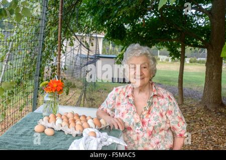 Senior woman posing beside tray of eggs on farm - Stock Photo