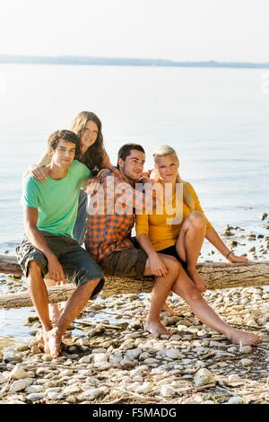 Friends sitting on driftwood next to shoreline looking at camera smiling, Schondorf, Ammersee, Bavaria, Germany - Stock Photo