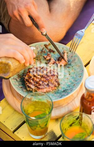 High angle view of two people cutting meat and pouring condiment onto plate - Stock Photo