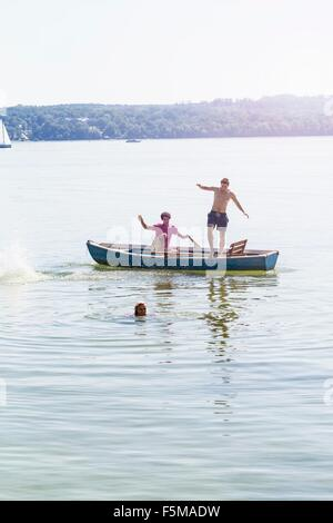 Friends jumping off boat and swimming in lake, Schondorf, Ammersee, Bavaria, Germany - Stock Photo