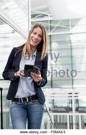 Young businesswoman using digital tablet at airport - Stock Photo