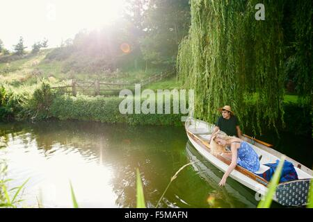 Young woman with boyfriend touching water from river  rowing boat - Stock Photo