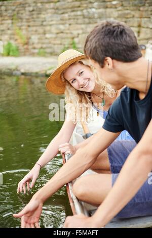 Young couple touching water from rowing boat on rural river - Stock Photo