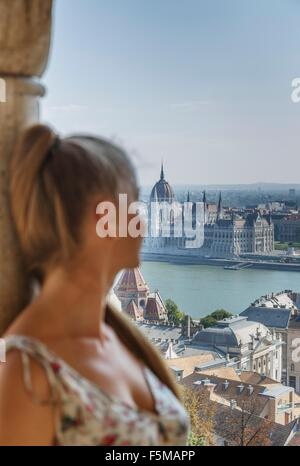 Mid adult woman looking at view of Buda from the Fisherman's Bastion, Budapest, Hungary - Stock Photo
