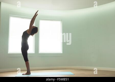 Mature woman doing yoga in curved room - Stock Photo