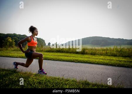 Young female runner stretching on rural park path - Stock Photo