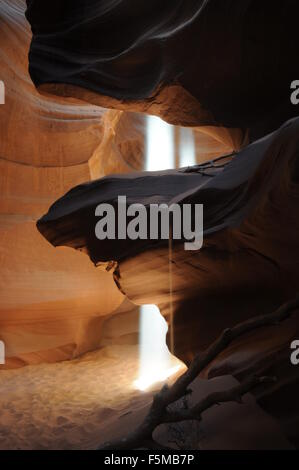 Upper Antelope Slot Canyon light beam with sand falling off rock in foreground - Stock Photo
