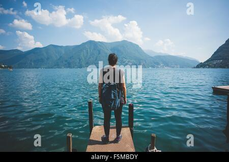 Rear view of mid adult woman looking out from pier, Lake Lugano, Switzerland - Stock Photo