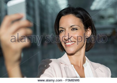 Mature businesswoman taking smartphone selfie at airport - Stock Photo