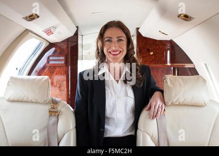 Portrait of female flight attendant on private jet - Stock Photo