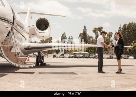 Female businesswoman shaking hands with private jet pilot at airport - Stock Photo