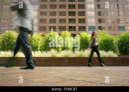 Businessman and woman walking in opposite directions - Stock Photo