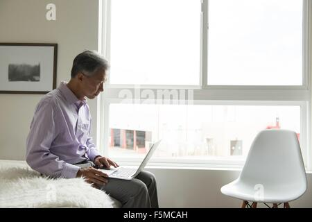 Side view of mature man sitting on edge of bed using laptop - Stock Photo
