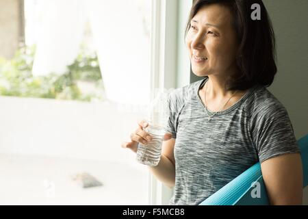 Mature woman holding rolled up yoga mat and bottle of water looking out of window smiling - Stock Photo