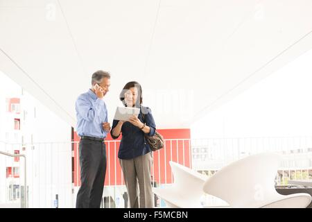 Mature couple standing using digital tablet and smartphone, looking down - Stock Photo