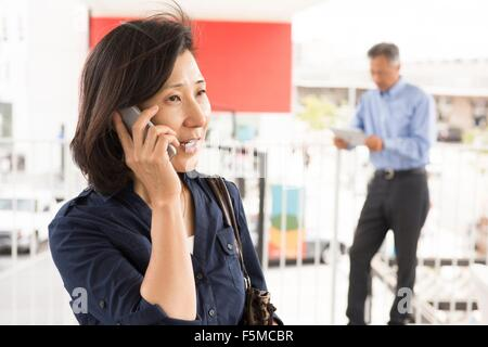 Head and shoulders of mature woman talking on smartphone looking away - Stock Photo