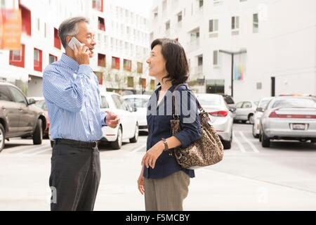 Side view of mature couple standing in parking lot face to face using cellular phone - Stock Photo