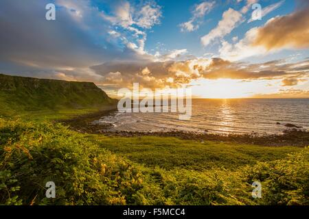 Sun setting on horizon over ocean, Giants Causeway, Bushmills, County Antrim, Ireland, UK - Stock Photo