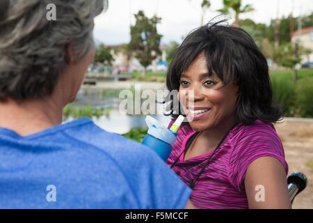 Two mature female friends sitting on park bench - Stock Photo
