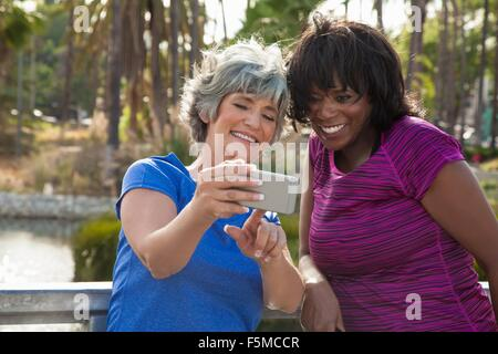Mature female friends in park, looking at smartphone, laughing - Stock Photo