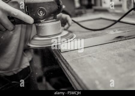 Wood artist working in workshop, using machinery, close-up - Stock Photo