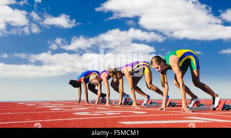 Four female athletes on starting blocks, about to start race - Stock Photo