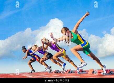 Four female athletes on athletics track, starting race - Stock Photo