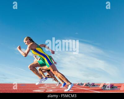 Three female athletes on athletics track, racing - Stock Photo