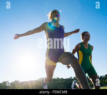 Two female athletes on athletics track, at end of race - Stock Photo