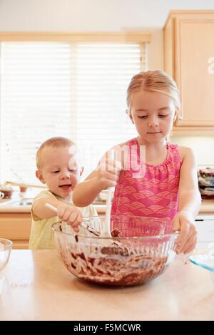Siblings melting chocolate in mixing bowl - Stock Photo