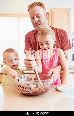 Family melting chocolate in mixing bowl - Stock Photo