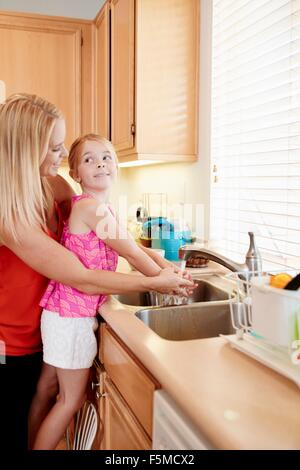 Mother washing daughter's hands in kitchen sink