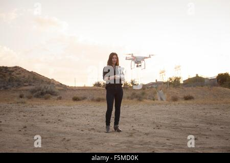 Female commercial operator on scrubland flying drone, Santa Clarita, California, USA - Stock Photo