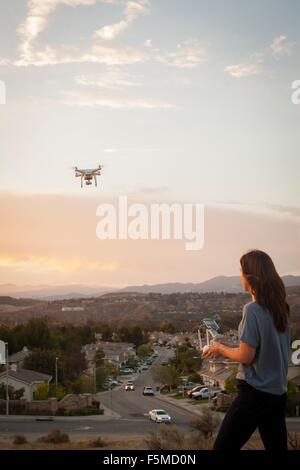 Female commercial operator flying drone above housing development, Santa Clarita, California, USA - Stock Photo