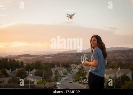 Female commercial operator flying drone above housing development, looking over shoulder at camera, Santa Clarita, - Stock Photo