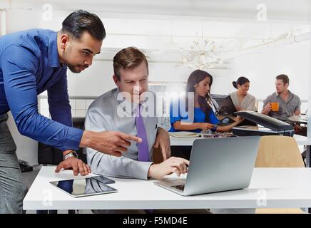 Two businessmen having discussion, looking at laptop, colleagues working in background - Stock Photo