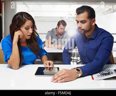 Businesswoman and businessman sitting at desk, looking at digital tablet - Stock Photo