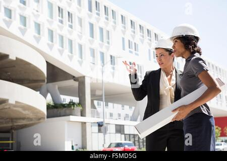 Two businesswomen, wearing hard hats, carrying plans - Stock Photo