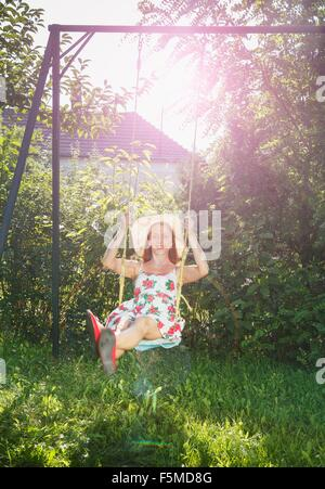 Mid adult woman swinging on garden swing - Stock Photo