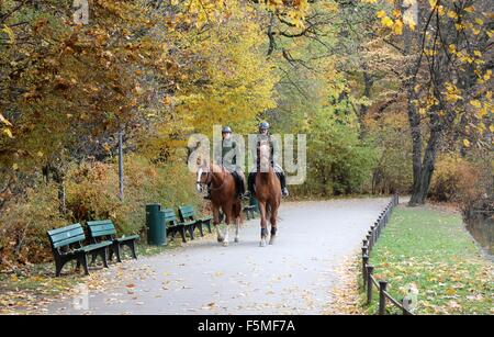 Two mounted police officers on patrol in the Englischer Garten Park in Munich, Germany. - Stock Photo