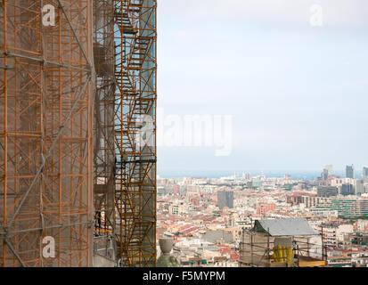 Construction site - scaffolding around new skyscraper against cityscape - Stock Photo