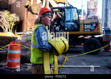 New York City, New York, USA.  October 29, 2015:  Construction worker walks with equipment. - Stock Photo