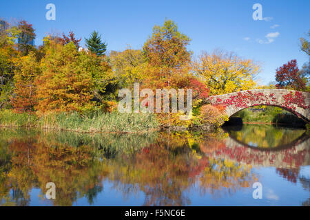 Colorful autumn view of Central Park in New York City at landmark Gapstow Bridge - Stock Photo
