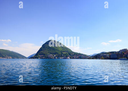 Lugano lake and mountains landscape. City, water, blue sky and mountains. Ticino, Swiss or Switzerland, Europe. - Stock Photo