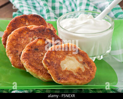 Cottage cheese pancakes on green plate - Stock Photo