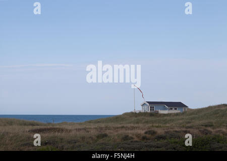 A summer house all alone stands on the very edge of a cliff top overlooking the North Sea proudly flying a pennant - Stock Photo