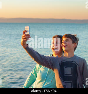 Young boy and a happy adult woman taking a selfie in front of a lake the boy has braces on his teeth - Stock Photo